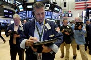 Trader William McInerney, center, works on the floor of the New York Stock Exchange, Friday, Aug. 10, 2018. Stocks are opening moderately lower on Wall Street following steeper losses in Europe, where investors worried about a sharp drop in Turkey's currency. (AP Photo/Richard Drew)
