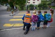 Stadtpolizist Edi Neuschwander begutachtet mit St.Galler Erstklässlern den Strassenverkehr vor einem Zebrastreifen. (Bild: Raphael Rohner)