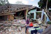 Eine Frau trocknet vor ihrem eingestürzten Haus ihre Wäsche. (AP Photo/Firdia Lisnawati)