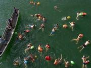 Teilnehmer des 38. Basler Rheinschwimmens werden von einem Dudelsackspieler begleitet bei ihrem Schwumm im Rhein durch die Stadt Basel am Dienstag, 14. August 2018. (KEYSTONE/Georgios Kefalas) (Bild: Keystone/GEORGIOS KEFALAS)
