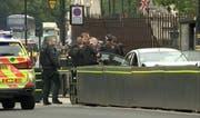 Die Polizei nimmt den Mann fest, der mit seinem Auto in die Absperrungen gefahren ist. (Bild: Keystone)
