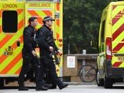 Schwer bewaffnete Polizisten am Dienstag in der Nähe des Tatorts. (Bild: Keystone/EPA/ANDY RAIN)