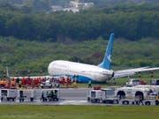 Über die Landebahn hinaus gerutscht: Die Maschine der chinesischen Fluggesellschaft Xiamen Airlines liegt nach der missglückten Landung neben der Piste im Gras. (Bild: KEYSTONE/AP/BULLIT MARQUEZ)