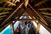 Touristen auf der Kapellbrücke. Nur wenige blicken nach oben in die leeren Brückengiebel. (Bild: Philipp Schmidli (Luzern, 29. Juli 2018))