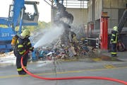 Angehörige der Feuerwehr Weinfelden wässern den Müllberg, der zuvor gebrannt hatte. Mit der Wärmebildkamera wird der Haufen auf Brandnester untersucht. (Bild: Mario Testa)