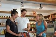 Laura Stoffel (links) und Christoph Rohrer vom Hilfswerk «Die fabelhafte Welt» begutachten eine Togobag. Romy Ineichen (rechts) ist eine der ehrenamtlichen Mitarbeiterinnen des Claro-Ladens, der sich für fairen Handel einsetzt. (Bild: Philipp Unterschütz, Sachseln, 21. August 2018)