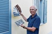 Ralph Brühwiler präsentiert vor seinem frisch renovierten Haus in Ebnat-Kappel die Prototypen der Karten, die er für sein Krinauer Kunstprojekt anfertigen lässt. (Bild: Anina Rütsche)