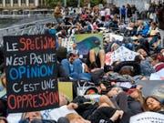 Auf einer Brücke legten sich die Demonstranten auf den Boden, um an die Qualen gefangener Fische zu erinnern. (Bild: KEYSTONE/MARTIAL TREZZINI)