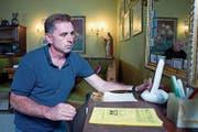 Stefan Bolli von der Alltagsassistenz der Pro Senectute Zug installiert ein digitales Telefon bei einem Kunden. (Bild: Maria Schmid (22. August 2018))