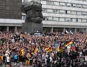 Rechte Gruppierungen versammelten sich am Montagabend bei der Karl-Marx-Statue in Chemnitz. (Bild: EPA/FILIP SINGER)