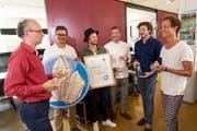 Michael Töngi, Mitglied des Alpenrats der Alpeninitiative, übergibt den Preis an die Mitglieder des Vereins Wasser für Wasser. (Bild: PD)