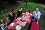 Ruth und Ruedi Zbinden sitzen mit ihrer Enkelin Maya und TZ-Praktikantin Viviane Vogel am gedeckten Tisch, hinter dem Waldlehrpfad. (Bilder: Sabrina Bächi)