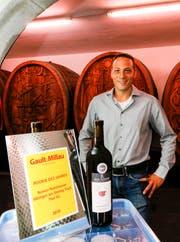 Roman Rutishauser mit der Gault-Millau-Auszeichnung im Weinkeller. Neben den Weissweinen «Kerner» und «Violine» war die Jury auch vom roten Cuvée «Grandezza» besonders angetan. (Bild: Rudolf Hirtl)