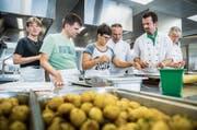 Unter Anweisung der Köche Gerhard Kiniger, Roger Stressle und Jürg Langer helfen die Bewohner in der Küche. (Bild: Andrea Stalder)