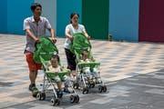 Das Reich der Mitte braucht dringend Nachwuchs: Eltern fahren ihre Zwillinge durch die Strassen Pekings spazieren. (Bild: Roman Pilipey/EPA; 10. August 2018)