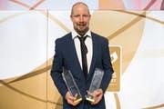 Der Uzwiler Mathias Seger mit dem Hockey Award für den «Most Popular Player» in der rechten und dem Special Award in der linken Hand. (Bild: Keystone/Daniel Teuscher)