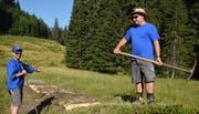 Ein Stück Prügelweg im «Rotibachried» auf der Alp Längenfeldmoos ist saniert. Vereinspräsident Tobias Pfister (links) und Vorstandsmitglied Silvan Gasser sind zufrieden. Bild: Robert Hess, Alpnach, 3. August 2018)