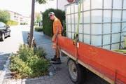 Mitarbeiter des Bauamtes sind mit einem grossen Wasserkanister unterwegs und versorgen junge Bäume mit der lebenswichtigen Flüssigkeit. (Bild: Susi Miara)