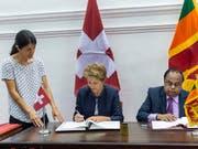 Bundesrätin Simonetta Sommaruga (Mitte) und der Innenminister von Sri Lanka, Seneviratne Bandara Nawinne (rechts), unterzeichnen das Memorandum of Understanding über eine Migrationspartnerschaft in Colombo. (Bild: KEYSTONE/PATRICK HUERLIMANN)