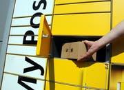 Ein Kunde holt sein Paket aus dem Automat My Post 24. (Bild: Markus von Rotz, Stans, 3. August 2018)