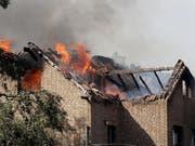 Flammen schlagen aus den Dachstühlen brennender Häuser an der Bahnstrecke in Siegburg. (Bild: Keystone/DPA/OLIVER BERG)