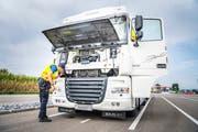 Kantonspolizist Matthias Brüschweiler prüft, ob am Lastwagen aus Weissrussland die Abgaswerte manipuliert werden. (Bild: Andrea Stalder)