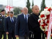 Präsident Giorgi Margwelaschwili (M) legte auf einem Friedhof bei Tiflis einen Kranz zum Gedenken an die getöteten georgischen Soldaten nieder. (Bild: KEYSTONE/EPA/ZURAB KURTSIKIDZE)