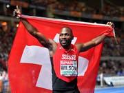 Alex Wilson feiert mit Schweizer Fahne seine Bronzemedaille (Bild: KEYSTONE/AP/MARTIN MEISSNER)