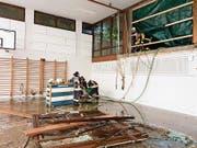 Nach dem schlimmen Unwetter von 8.Juni: Feuerwehrleute pumpen Wasser aus der unteren Reutenen-Turnhalle. (Bild: PD)