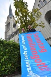 Die Pfarrer Markus Keller und Lukas Butscher entrollen die neue Blache vor der Kirche. (Bild: Manuel Nagel)