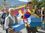 Mitglieder der Gesellschaft für bedrohte Völker (GfbV) und Tibet-Organisationen reichen bei der Bundeskanzlei eine Petition ein, mit der sie Politik und Behörden auffordern, die Grundrechte der Tibeterinnen und Tibeter in der Schweiz zu schützen. (Bild: KEYSTONE/ALESSANDRO DELLA VALLE)