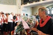Die Sängerinnen und Sänger verabschieden Seniorenchor-Gründerin und -Dirigentin Barbara Laager mit Blumen. (Bild: Manuela Olgiati)