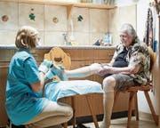 Sara Barmettler hilft einer älteren Frau beim Anziehen der Strümpfe. (Bild: Herbert Zimmermann)