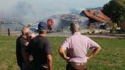 Anwohner beobachten den Brennenden Stall. (Bild: Roman Scherrer)