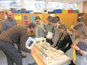 Bauleiter Christophe Zemp (links) und Architekt Matthias Lötscher zeigen den Schülern anhand eines Modells, wie das Schulareal in Meggen künftig aussehen wird. (Bild: Jolina Quadrelli und Raoul Schäfer)