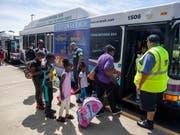 Familien steigen in einen Evakuierungsbus in der US-Stadt Raleigh im Bundesstaat North Carolina. (Bild: KEYSTONE/EPA/JIM LO SCALZO)
