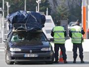 Französische Polizisten kontrollieren ein Auto an der Grenze zu Italien in La Turbie. (Bild: KEYSTONE/AP/LIONEL CIRONNEAU)