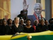Kofi Annans Sohn Kojo Annan (l.) seine Witwe Nane Annan (2.v.l.), Tochter Ama Annan (M) und weitere Familienmitglieder am Donnerstag am Sarg des früheren Uno-Generalsekretärs. (Bild: Keystone/AP/SUNDAY ALAMBA)