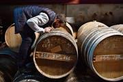 Ein Cognac-Produzent riecht zur Qualitätskontrolle am reifenden Inhalt im Fass. (Bild: Nicolas Tucat/AFP (Segonzac, 9. Februar 2018)