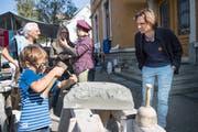 Auch die Steinbildhauerin führt einen kleinen Besucher in ihr Handwerk ein. (Bild: Ralph Ribi)