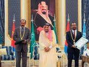 Der eritreische Präsident Isaias Afwerki (l) und der äthiopische Premierminister Abiy Ahmed haben in Dschidda im Beisein des saudischen Königs Salman einen Freundschaftsvertrag unterzeichnet. (Bild: KEYSTONE/AP Saudi Press Agency)