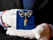 Eine Brosche, die einst im Besitz der französischen Königin Marie-Antoinette war, wird bei einer Präsentation von Juwelen aus dem Haus Bourbon-Parma beim Auktionshaus Sotheby's von einem Mitarbeiter gehalten. Die Versteigerung ist für den 14. November 2018 angekündigt. (Bild: Keystone/DPA/TOBIAS HASE)