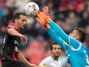 Xamax-Spieler Raphael Nuzzolo kommt gegen St. Gallens Keeper Dejan Stojanovic zu spät (Bild: KEYSTONE/LAURENT GILLIERON)