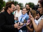 U2-Sänger Bono spricht mit Fans, nachdem er vergangene Woche mit der deutschen Kanzlerin Angela Merkel über Entwicklungshilfe in Afrika gesprochen hat. Bei einem Konzert in Berlin hat am Samstag seine Stimme versagt und die Veranstaltung musste abgebrochen werden. (Bild: KEYSTONE/EPA/CLEMENS BILAN)