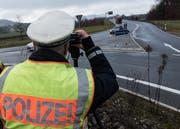 Ein Polizist kontrolliert Gottmadingen am Ende der Autobahn A81 mit einem Lasermessgerät die Geschwindigkeit der Fahrzeuge. Auf der A81 nahe der Schweizer Grenze kommt es häufig zu illegalen Autorennen. (Bild: DPA)