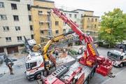Bergungsarbeiten nach dem Kranunglück: Mit einem Pneukran wird der umgestürzte Kran entfernt. (Bilder: Hanspeter Schiess)