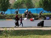 Nach einem Angriff auf eine Militärparade im Iran versuchen sich Zivilisten in Sicherheit zu bringen - mindestens 29 Menschen wurden getötet, dutzende weitere verletzt. (Bild: KEYSTONE/AP Mehr News Agency/MEHDI PEDRAMKHOO)