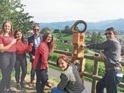 Freuen sich über die neue Wegmarke «Aussichtsfenster»: Tom Bertényi (Dritter von links), Carola Espanhol (Zweite von rechts), Ivo Herrsche und drei Mädchen von den OMR Voices. (Bild: pd)