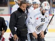 Luganos Verteidiger Thomas Wellinger wird von einem Staff-Mitglied vom Eis begleitet (Bild: KEYSTONE/DANIEL TEUSCHER)