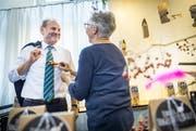 Vögeli trifft auf Vögeli: Marianne Boltshauser vom Geschenkladen Frappant steckt dem Gemeindepräsidenten einen Deko-Vogel an. (Bild Andrea Stalder)